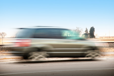 A fast moving car on a rural highway blurred as the driver hurries to get to his workplace.