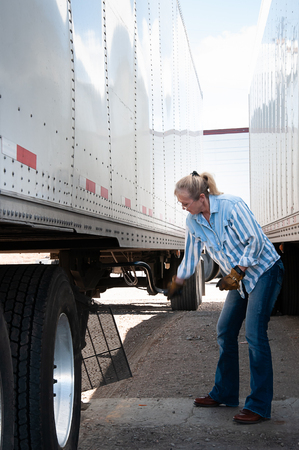 A woman truck drivers hand blurs as she cranks up the landing gear after backing under a loaded trailer ready to to on the road. Stock Photo