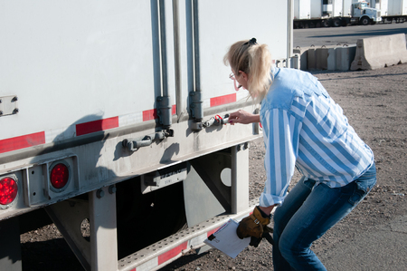 Woman truck driver checking her trailer seal number to make sure it matches the numbers on her bill of lading.