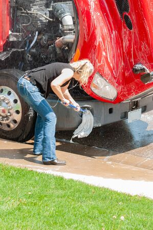 Woman truck driver washing semi-truck while she waits for her D.O.T. 70 hour reset.