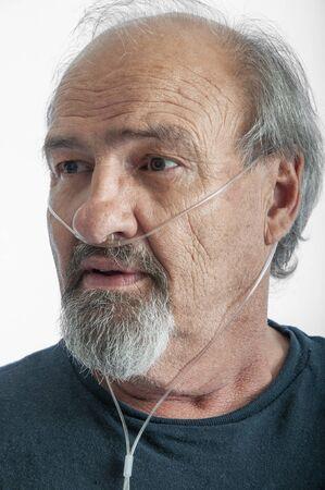 Uomo adulto che indossa una cannula O2 per l'enfisema
