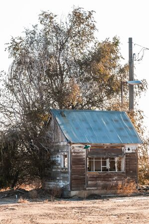 Run down shack of a former scale house under a winter tree