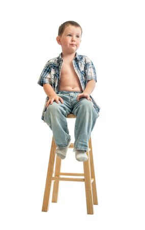 Little boy waits nervously on a wooden stool at the Doctors office for a check up.