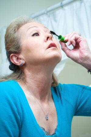 Adult woman applying mascara to her eye-lashes to make them longer Standard-Bild
