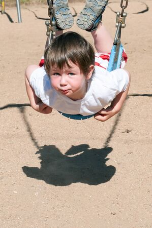 Cute little boy too short to sit in the larger swings