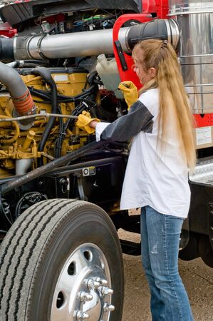 Woman truck driver checking the oil level on a big truck Stock Photo