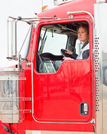 Woman Truck Driver looking out the window while driving a big rig Stock Photo
