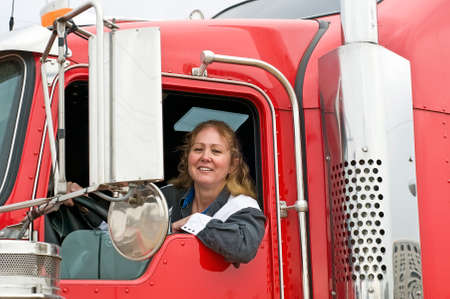 Woman truck driver leaning out the drivers side window.