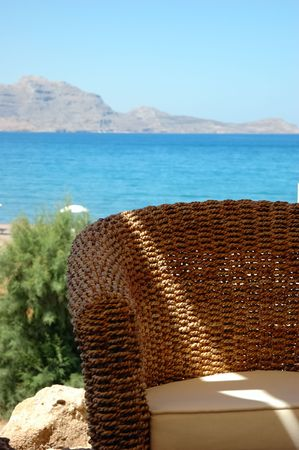 Detail of the chair of a beach bar, sea view in background Stock Photo - 1320655