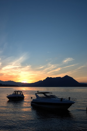Small yachts anchored in quite lake water before the dawn; Maggiore Lake, Italy. photo