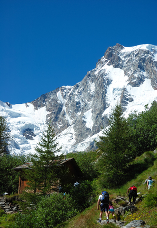 Group of trekkers walking on a path in front of the east face of Monte Rosa peak, west alps, Italy. photo