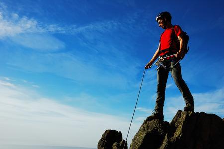 orientation: Rock climber, partial cloudy sky, horizontal orientation Stock Photo