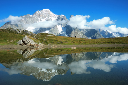 View of the south face of Mont Blanc mountain range reflected in a lake, while two trekkers walking along the path. Val Veny, Italy. photo