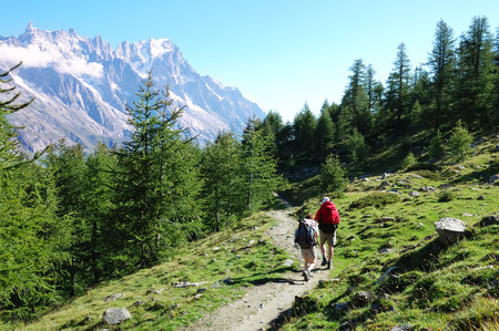 blanc: Trekkers walking along a mountain path, Mont Blanc valley, west Alps, Italy.