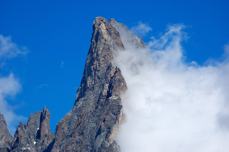 noire: Aiguille Noire (Mont Blanc, Italy) rocky peak, while a growing cloud try to climb it. Stock Photo