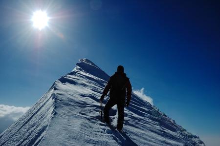 stijger: Een eenzame klimmer het bereiken van de top van de berg Stockfoto