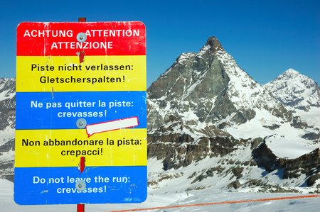 Warning about leaving marked and protected piste Do not leave the run: crevassses!; against a mountain background (Matterhorn, Zermatt, Swiss). photo