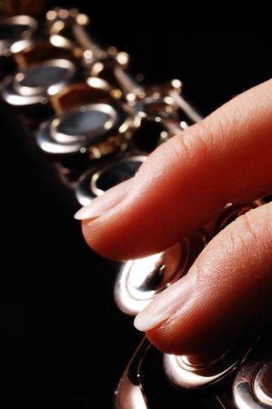 Close-up photo of flautist fingers, black background photo