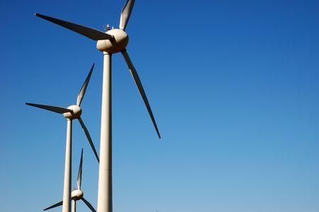 Eolic power generator: windmills over blue sky  photo
