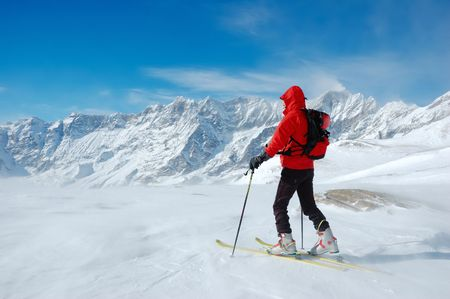 A lonely backcountry skier in a sunny winter day, alpine scenic, horizontal orientation photo