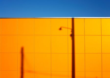 lampost: Urban landscape: modern yellow wall with lampost shadow