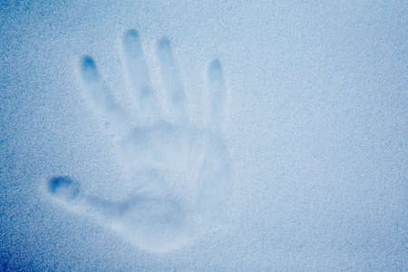 snowscene: Snow with an impression of a handprint; cold tone. Stock Photo