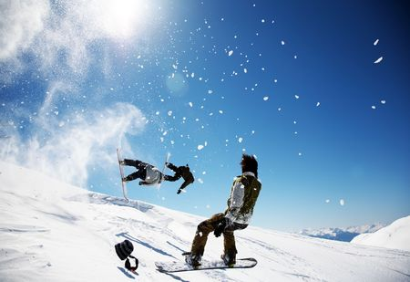 aosta: Snowboarders launching off a jump; La Thuile , Aosta, Italy.
