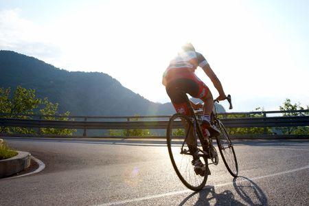 Ciclista de equitación cuesta arriba en una carretera de montaña, Italia