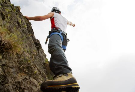 vibrant colours: White young male rock-climber, summer season, upward view, horizonzal frame, vibrant colours, back-light, copy-space on the right