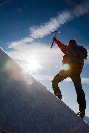 Lone male mountain climber climbing a snowy ridge; Mont Blanc, Europe.