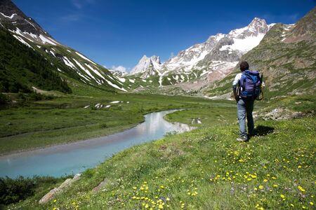 courmayeur: Hombre caminante disfrutar de las vistas sobre el hermoso paisaje del lago Combal, Val Veny, Courmayeur, Italia  Foto de archivo