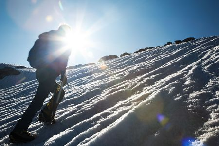backpacking: Lone male mountain climber climbing a snowy ridge; Mont Blanc, Europe.