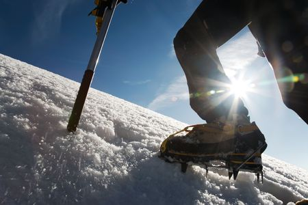 expeditions: Mountain climber: detail on boot with ice crampon and ice axes; back-light Stock Photo