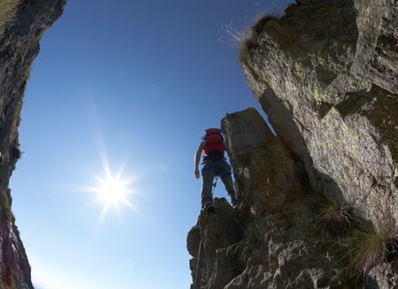terrific: Terrific view of a climbing rote: climber standing on the rocky ridge, back-light, fish-eye lens.
