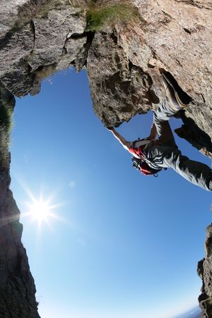 terrific: Terrific view of a climbing route: young man climbing a rocky ridge, back-light, fish-eye lens, vertical frame.