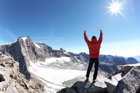 stijger: Teken van de overwinning: klimmer op de top van de berg. Nationaal park Gran Paradiso, Italië Stockfoto