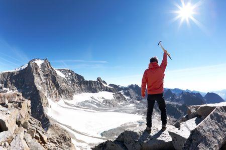 Signo de la victoria: escalador en la cima de la montaña. Parque Nacional de Gran Paradiso, Italia  Foto de archivo