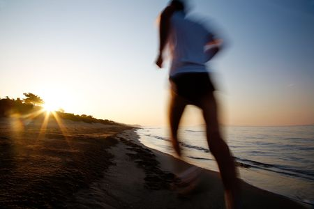 Young male runner running on a empty beach at dawn. Blur effect.