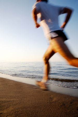 Young male runner running on a empty beach at dawn. Blur effect. photo