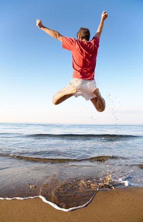 Back view of young man jumping on the beach: happiness and energy concept Standard-Bild