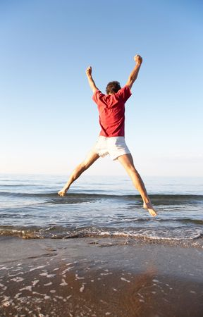 Back view of young man jumping on the beach: happiness and energy concept photo