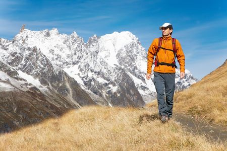 Male trekker walks along a mountain path, in background the Grand Jourasses peaks, fall season, Val Veny, Mont Blanc massif, Courmayeur, Italy photo