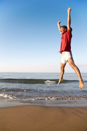 Young man takes a great leap on a beach at sunrise: happiness, fitness, success concept photo