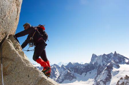 Climber climbing a rocky wall; horizontal frame. Aiguille du Midi, Mont Blanc massif, Chamonix, France. In background the north face of Grand Jurasses peaks. Wiki: http://en.wikipedia.org/wiki/Aiguille_du_Midi Standard-Bild