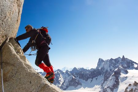 terrific: Climber climbing a rocky wall; horizontal frame. Aiguille du Midi, Mont Blanc massif, Chamonix, France. In background the north face of Grand Jurasses peaks. Wiki: http:en.wikipedia.orgwikiAiguille_du_Midi Stock Photo