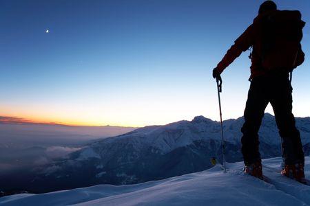 arri�re-pays: Au cr�puscule, un brave skieur arri�re pour atteindre le sommet de la montagne apr�s une longue journ�e de marche dans le d�sert. D'aventure et d'exploration concept.