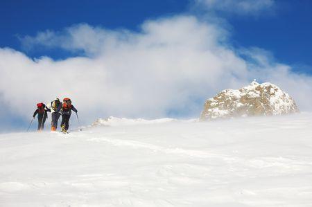 arri�re-pays: Un groupe de skieurs marche arri�re au sommet de la montagne dans le blizzard, Alpes italiennes, europe.