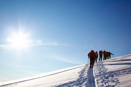 arri�re-pays: Un groupe de skieurs marche arri�re au sommet de la montagne sur un ciel bleu azur, Alpes italiennes, europe.