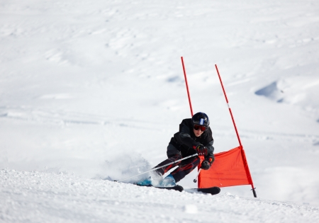 Young skier doing downhill on Giant Slalom course; horizontal orientation, large copy space.