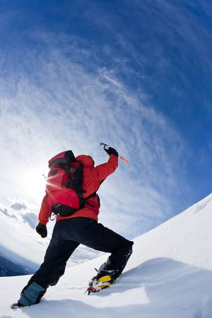 Mountaineer reaching the top of a snowcapped mountain peak. Vertical frame. Stock Photo - 4331535